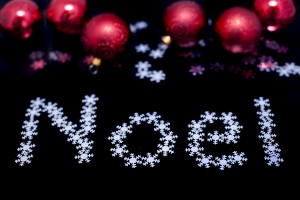Noel greeting card with text in tiny snowflakes and colourful red Christmas baubles on a dark background