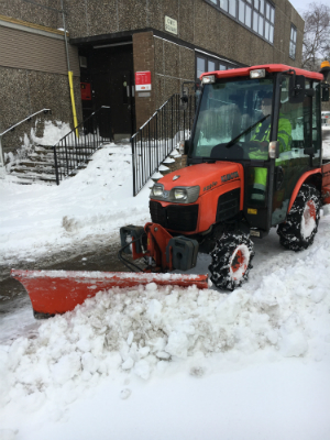A mini-tractor with a snow plough on the front clears snow from a pavement.