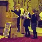 Children from Loretto, St. Gabriel's and St. Martin's lead the Liturgy of the Word. Chloe from P7 (middle) prepares to sing the psalm.