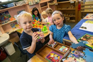 Boy and girl playing with puzzles at a nursery table
